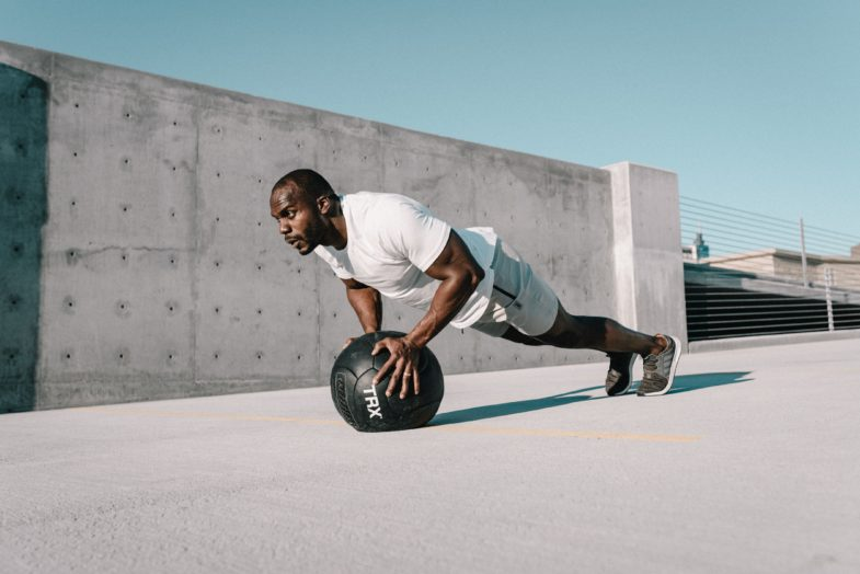 man in white t-shirt and black pants playing with black soccer ball. Medicine Ball Explosive Pushup